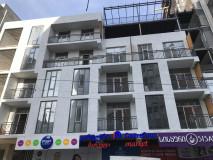 Продается квартира в начале Багеби в новом доме с белым каркасом. Квартира открыта, все коммуникации внутри, вставлены коричневые пластиковые двери и железная дверь.